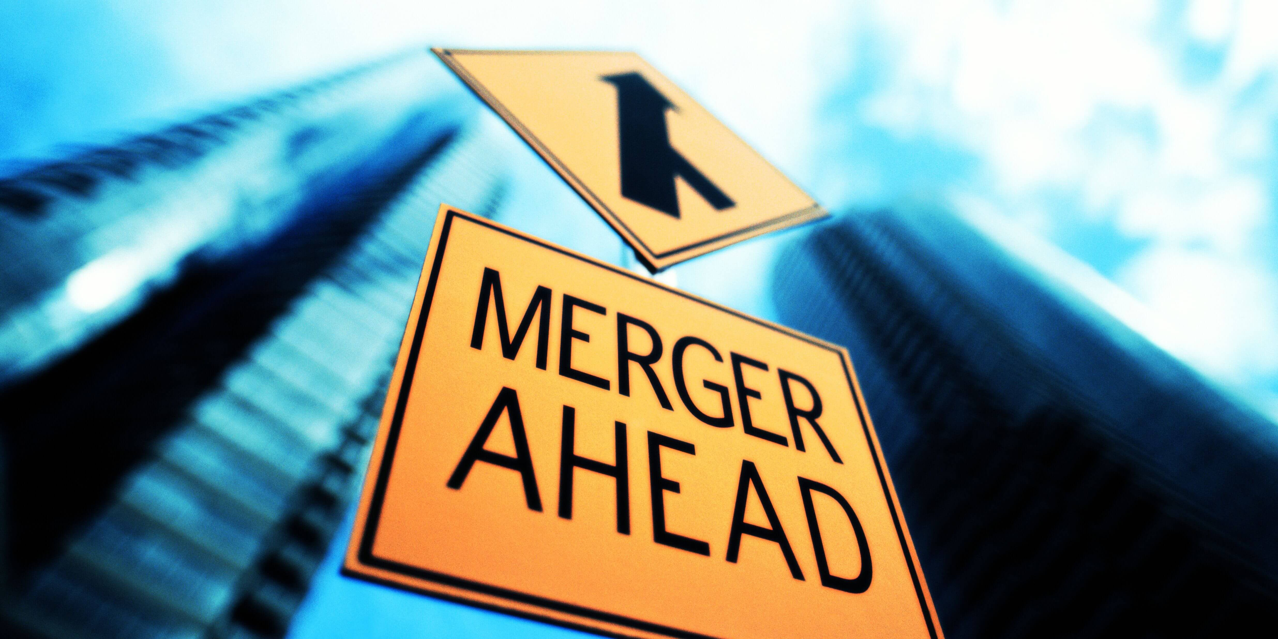 merger-sign-below-office-building